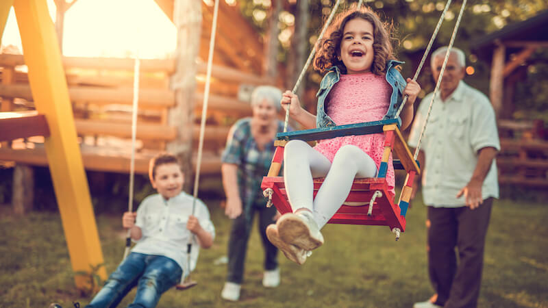 Kids on swing with grandparents